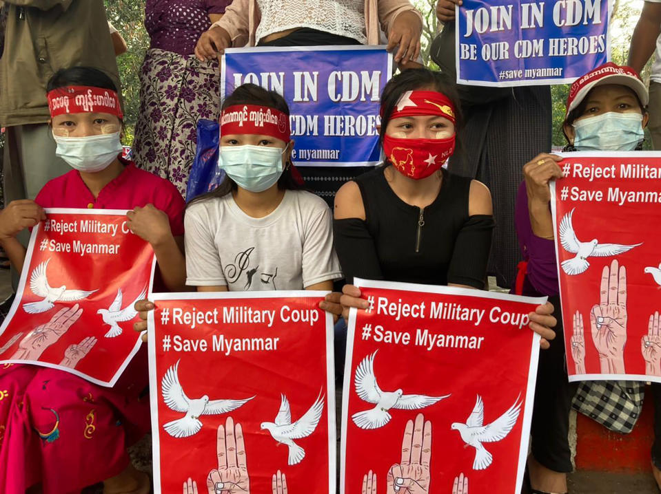 """Anti-coup protesters hold posters that read """"#Reject Military Coup #Save Myanmar"""" as they gather under an elevated roadway just outside the Hledan Centre in Yangon, Myanmar Monday, Feb. 22, 2021. A call for a Monday general strike by demonstrators in Myanmar protesting the military's seizure of power has been met by the ruling junta with a thinly veiled threat to use lethal force, raising the possibility of major clashes. (AP Photos)"""