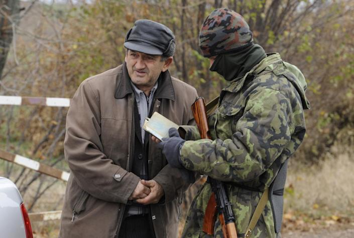 A Ukrainian soldier looks at the ID of a man at a checkpoint in the eastern village of Bugas, on October 24, 2014 (AFP Photo/Alexander Khudoteply)