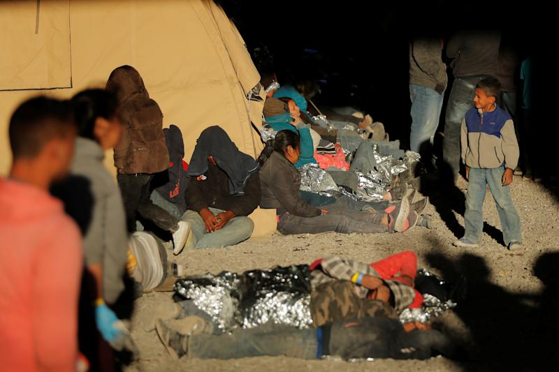 A young boy walks near other migrants lying on the ground inside an enclosure, where they are being held by U.S. Customs and Border Protection (CBP), after crossing the border between Mexico and the United States illegally and turning themselves in to request asylum, in El Paso, Texas, U.S., March 29, 2019. Photo: Lucas Jackson/Reuters)