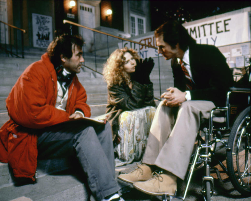 American actors Kyra Sedgwick and Tom Cruise, with director Oliver Stone, on the set of his movie Born on the Fourth of July, based on the book by Ron Kovic. (Photo by Universal Pictures/Sunset Boulevard/Corbis via Getty Images)