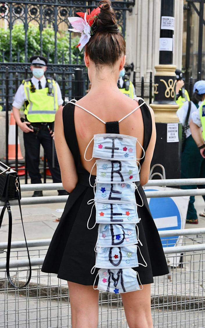 A protester wears 'freedom' written on face masks on her back. An anti lockdown and anti-vaccine demonstration took place as almost all Covid-19 restrictions are lifted in England - Michael Melia/Avalon
