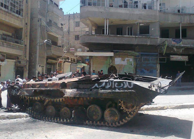 """In this citizen journalism image provided by Edlib News Network ENN, anti-Syrian regime citizens look at a Syrian military tank with Arabic that reads, """"Assads' dogs,"""" that was damaged during  clashes between rebels and Syrian government forces, at the northern town of Ariha, in Idlib province, Syria, Monday, June 4, 2012. European leaders are expected to press the contentious issue of Syria at a European Union-Russian summit Monday in St. Petersburg, but few believe Russian President Vladimir Putin will agree to ramp up pressure on the Syrian government. (AP Photo/Edlib News Network ENN) THE ASSOCIATED PRESS IS UNABLE TO INDEPENDENTLY VERIFY THE AUTHENTICITY, CONTENT, LOCATION OR DATE OF THIS HANDOUT PHOTO"""