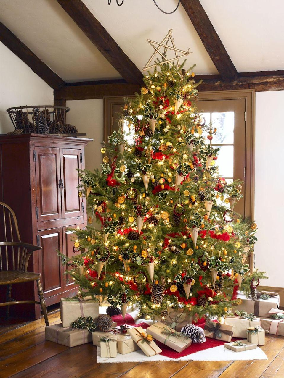 <p>Crowned with a twig star and wrapped with a garland of red burlap, this towering tree packs in the DIY treats: dried orange slices, walnuts gilded with gold paint, mini cranberry wreaths, and more.</p>
