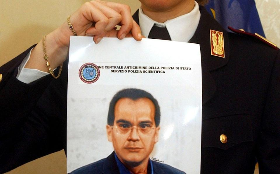A police officer shows a computer generated image of Mafia top boss Matteo Messina Denaro, at the Palermo police headquarters, southern Italy in 2007 - Alessandro Fucarini /AP