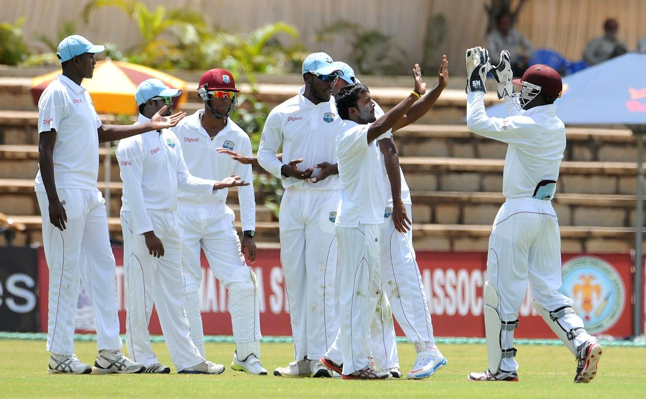 West Indies A team players celebrates after the wicket of India A team, during the unofficial 1st Test Match between India A and West Indies A 3rd day at Gangothri Glades Cricket Ground, in Mysore on Sept. 27, 2013.(Photo: IANS)