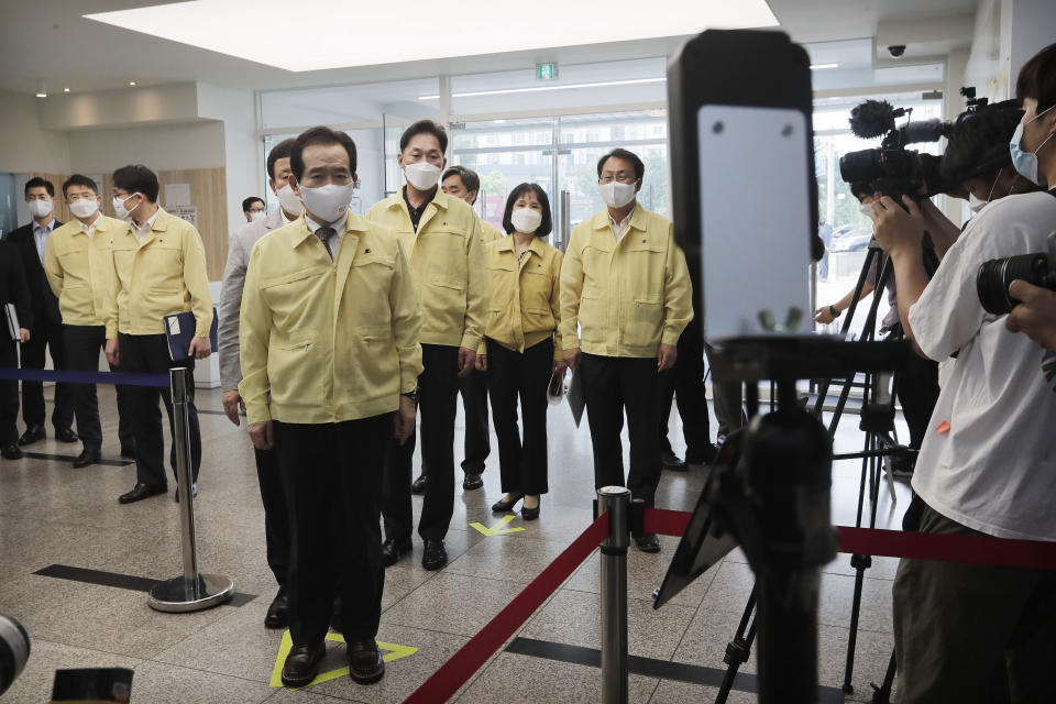 South Korean Prime Minister Chung Sye-kyun, fifth from left, stands to have his body temperature checked upon his arrival at a private educational academy to check the prevention measures of the new coronavirus in Seoul, South Korea, Thursday, July 2, 2020. South Korea reported dozens of new cases as the virus continues to spread beyond the capital area and reach cities like Gwangju, which has shut schools and tightened social restrictions after dozens were found infected this week. (AP Photo/Ahn Young-joon)