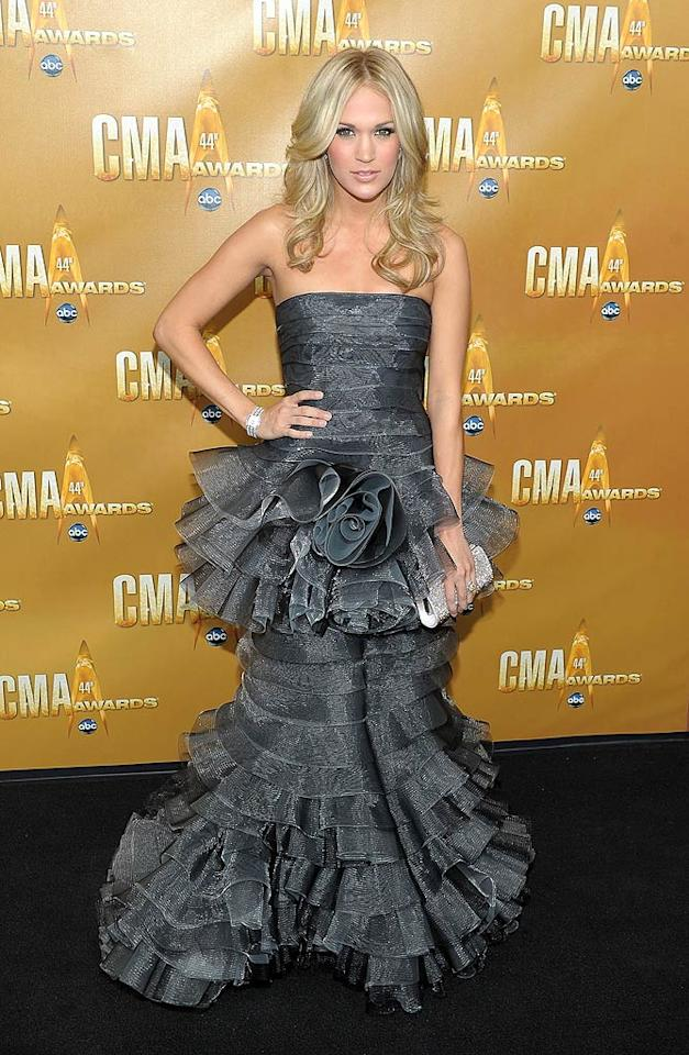 "CMA hostess with the mostest Carrie Underwood, who donned a number of ensembles throughout the evening, started things off on the wrong foot thanks to her steel gray eyesore, which featured multiple tiers and a bizarre rosette. Michael Loccisano/<a href=""http://www.wireimage.com"" target=""new"">WireImage.com</a> - November 10, 2010"