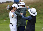 Jin Young Ko, left, of South Korea, celebrates with her parents on the 18th green after winning the LPGA Cambia Portland Classic golf tournament in West Linn, Ore., Sunday, Sept. 19, 2021. (AP Photo/Steve Dipaola)