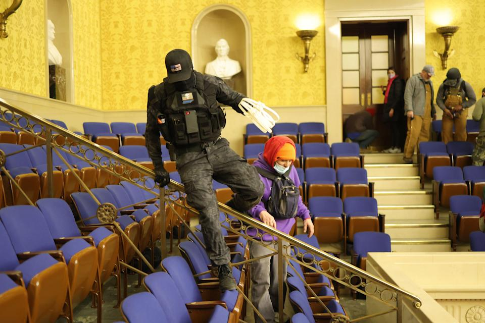 A man in camouflage swinging plastic hand restraints, identified by law enforcement as Eric Munchel, jumps among seats in the Capitol after it was stormed Jan. 6.