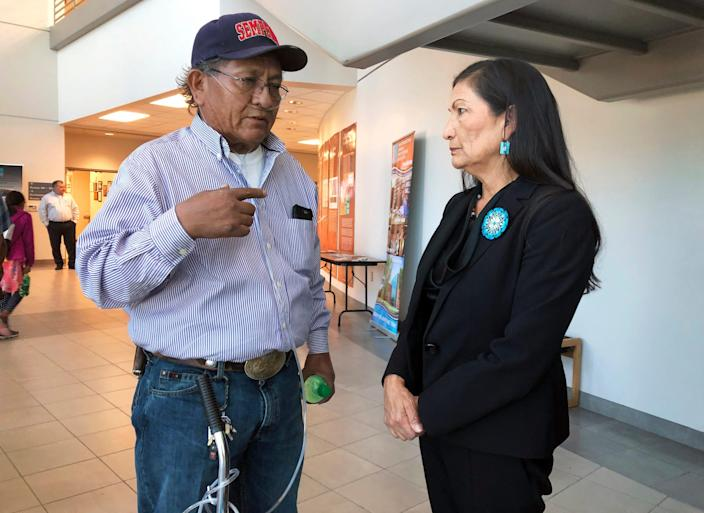 Leslie Begay, left, speaks with Rep. Deb Haaland, D-New Mexico, in a hallway outside a congressional field hearing in 2019 in Albuquerque, N.M.