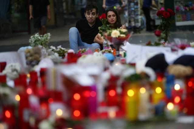<p>A couple looks at flags, messages and candles placed after van attack that killed at least 13, in central Barcelona, Spain, Saturday, Aug. 19, 2017. Police on Friday shot and killed five people carrying bomb belts who were connected to the Barcelona van attack, as the manhunt intensified for the perpetrators of Europe's latest rampage claimed by the Islamic State group. (AP Photo/Manu Fernandez) </p>