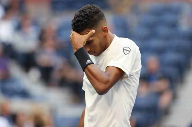 Felix Auger-Aliassime of Canada reacts after losing a point to Daniil Medvedev of Russia during their Men's Single semifinal match on Day Twelve of the 2021 US Open at the USTA Billie Jean King National Tennis Centre. (Elsa/Getty Images - image credit)