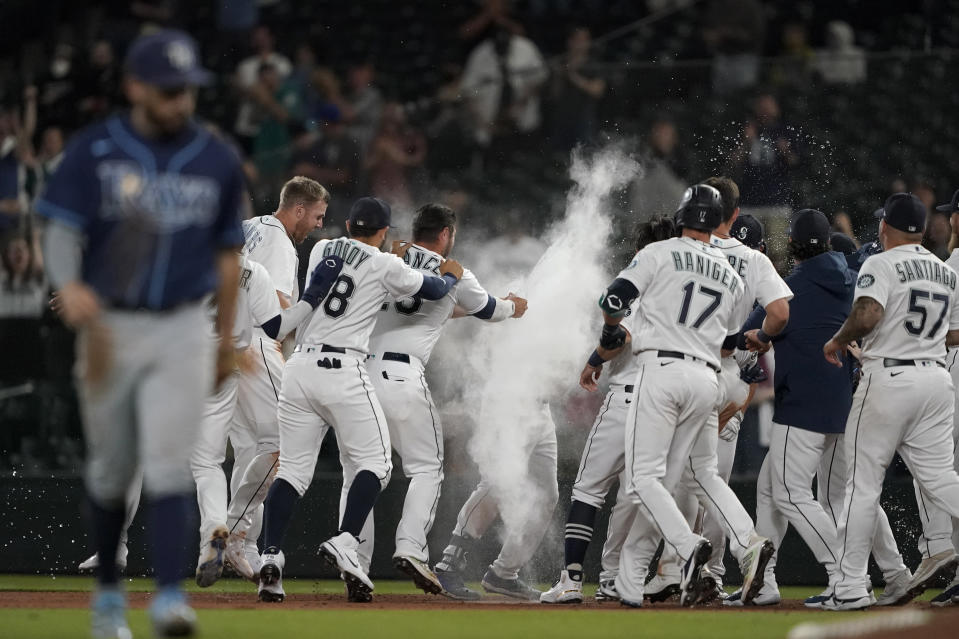 Seattle Mariners' Kyle Seager, center, is covered in powder by teammates after after he drove in the winning run with a single in the ninth inning of the team's baseball game against the Tampa Bay Rays, Thursday, June 17, 2021, in Seattle. Rays' Brandon Lowe, foreground left, heads off the field. The Mariners won 6-5. AP Photo/Ted S. Warren)