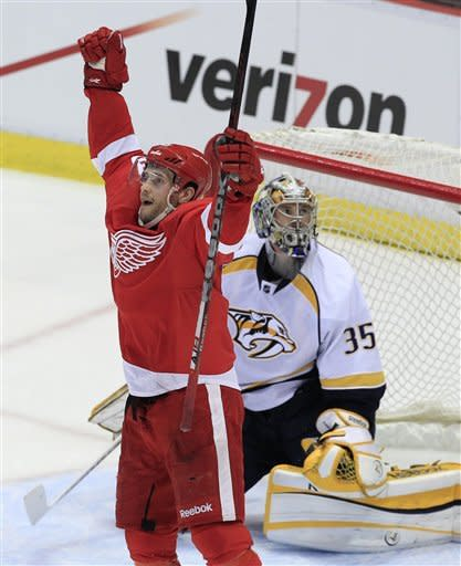Detroit Red Wings center Pavel Datsyuk (13), of Russia, celebrates his goal on Nashville Predators goalie Pekka Rinne (35), of Finland, during the second period of Game 3 of an NHL hockey Stanley Cup first-round playoff series in Detroit, Sunday, April 15, 2012. (AP Photo/Carlos Osorio)