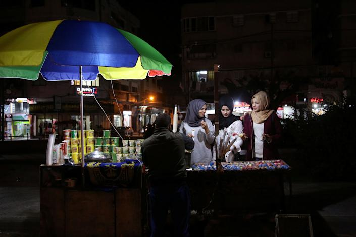 From left: Palestinian Saly Abu Amra, 23, Hana Abu El-Roos, 18, and Wessal Abu Amra, 17, buy snacks from a vendor in Gaza City. (Photo: Samar Abo Elouf/Reuters)
