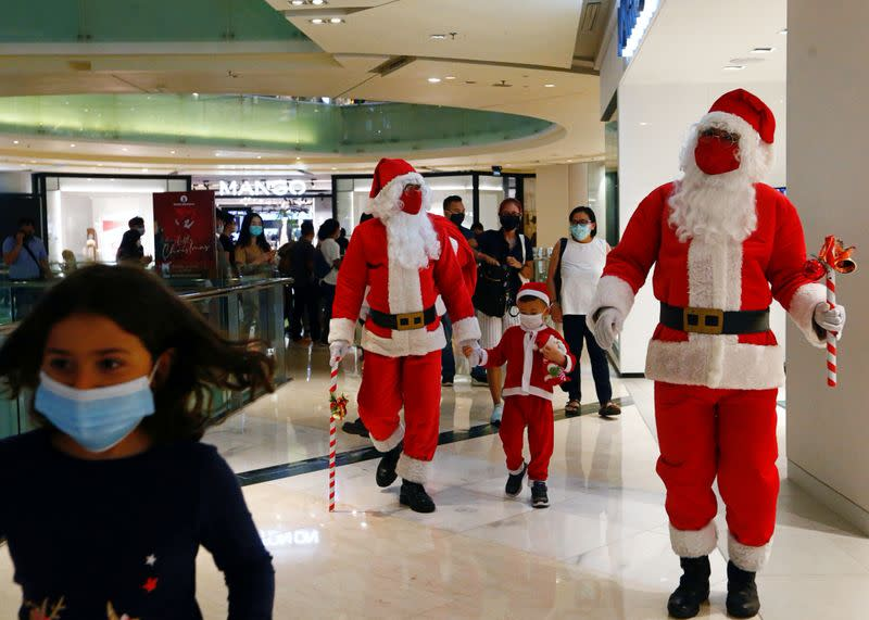 FILE PHOTO: People wearing Santa Claus costumes greet people in a shopping mall amid the coronavirus disease (COVID-19) outbreak in Jakarta