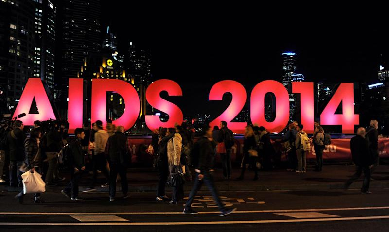 People gather next to a sign reading AIDS 2014 in Melbourne on July 18, 2014 after news that downed Malaysia Airlines flight MH17 was carrying many participants headed to the 20th International AIDS Conference planned in the Australian city (AFP Photo/)
