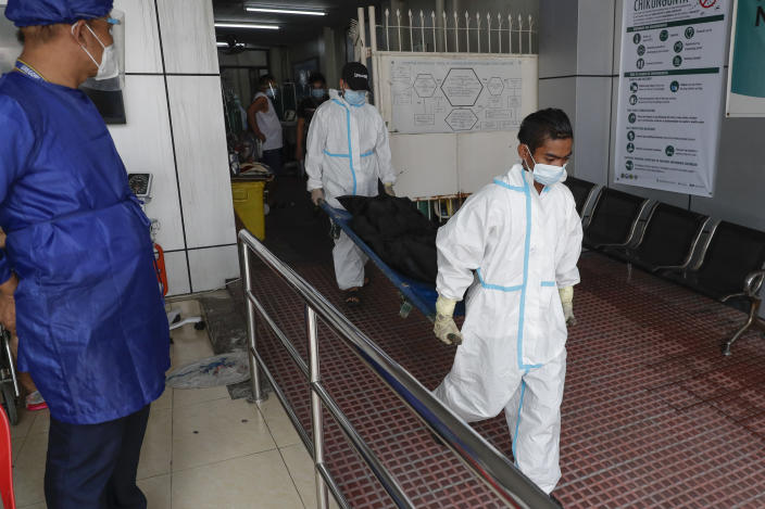 Funeral workers wearing protective suits carry a person who died due to COVID-19 complications at a hospital in Manila, Philippines on Monday, April 26, 2021. COVID-19 infections in the Philippines surged past 1 million Monday in the latest grim milestone as officials assessed whether to extend a monthlong lockdown in Manila and outlying provinces amid a deadly spike or relax it to fight recession, joblessness and hunger. (AP Photo/Aaron Favila)
