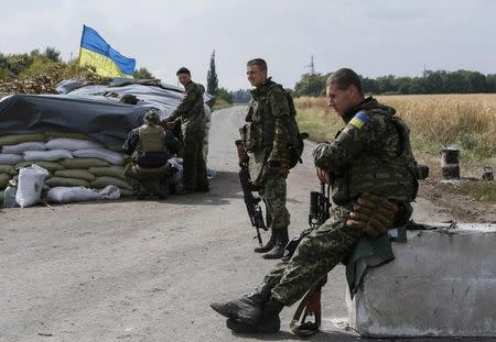 Members of the Ukrainian national guard are seen at a checkpoint nearby the town of Slavyanoserbsk, in Luhansk region September 10, 2014. Ukraine's president said on Wednesday Russia had removed the bulk of its forces from his country, raising hopes for a peace drive now underway after five months of conflict in which more than 3,000 people have been killed. REUTERS/Gleb Garanich