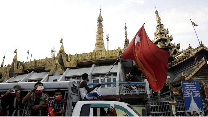 A demonstrator waves a flag of the National League for Democracy (NLD) party, led by detained Myanmar State Counsellor Aung San Suu Kyi
