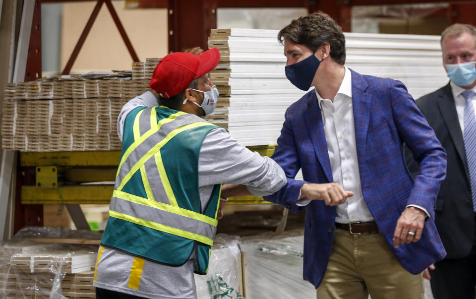 Canada Prime Minister Justin Trudeau elbow bumps elbows with an employee as he tours the AAA Door company in Calgary, Alberta, Wednesday, July 7, 2021. (Jeff McIntosh/The Canadian Press via AP)