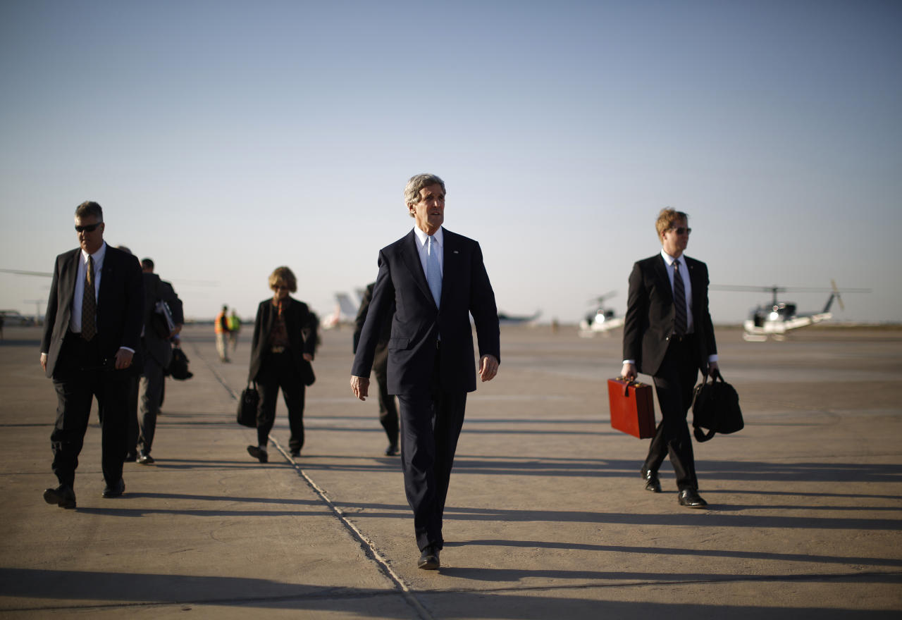 U.S. Secretary of State John Kerry, second right, walks across the tarmac of Baghdad International Airport as he prepares to board an aircraft out of the Iraqi capital Sunday, March 24, 2013. Kerry was in Iraq today, meeting with officials in an unannounced visit. He says he made it clear in talks with the Iraqi Prime Minister Nouri al-Maliki that the U.S. is unhappy with Iraq for letting Iran use its airspace to ship weapons and fighters to Syria. (AP Photo/Jason Reed, Pool)