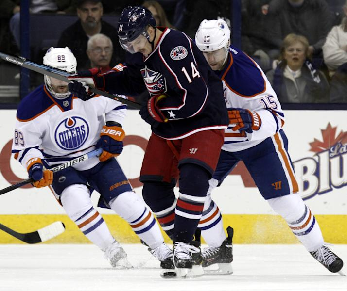Columbus Blue Jackets' Blake Comeau (14) works for the puck between Edmonton Oilers' Sam Gagner (89) and Nick Schultz (15) in the first period of an NHL hockey game in Columbus, Ohio, Friday, Nov. 29, 2013. (AP Photo/Paul Vernon)