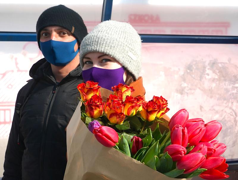 A couple with face masks walk with tulips on March 26, 2020 on a street of Warsaw, amid the novel coronavirus pandemic. - Polish government urged citizens to stay at home for a few weeks to limit the spread of the novel coronavirus. (Photo by JANEK SKARZYNSKI / AFP) (Photo by JANEK SKARZYNSKI/AFP via Getty Images)
