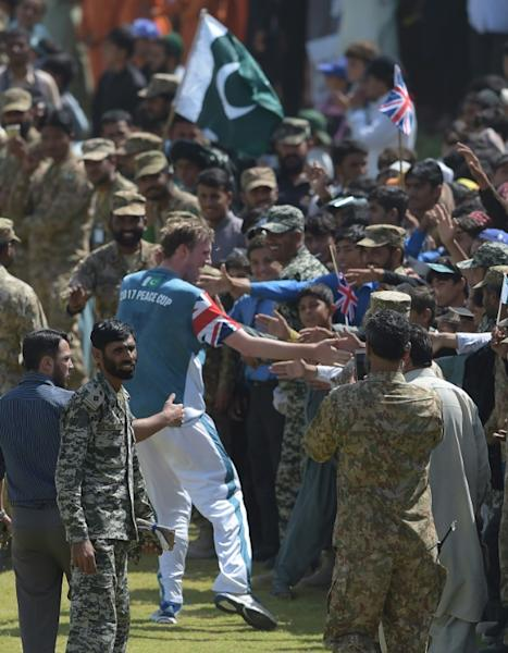 UK Media XI cricketer (C) shakes hands with cricket fans during a T20 cricket match between Pakistan XI and UK Media XI at the Younis Khan Cricket Stadium in Miranshah, the former stronghold of Al-Qaeda and Taliban militants, in North Waziristan