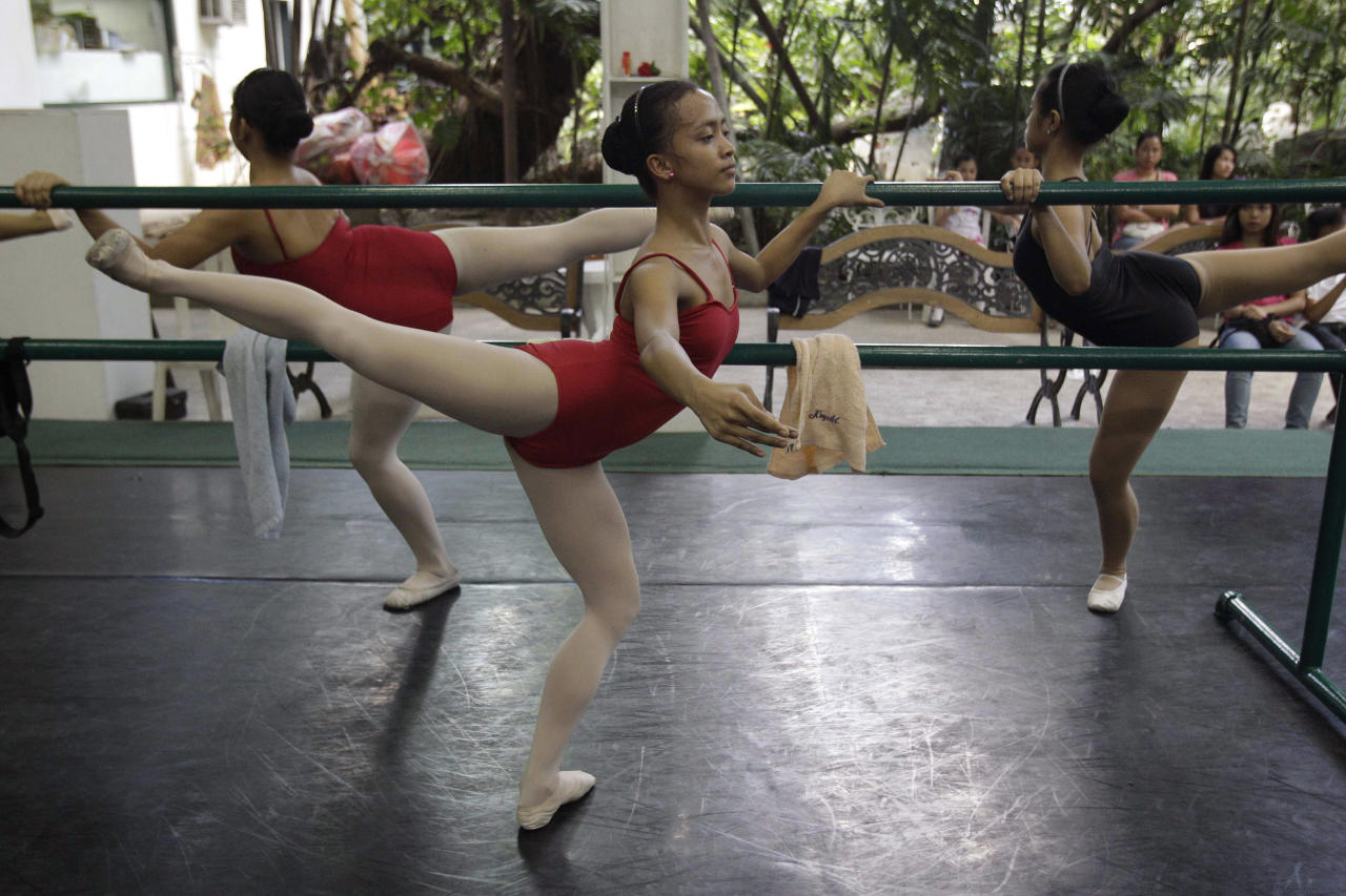 In this photo taken Nov. 25 2012, Filipino slum dweller Jessa Balote, center, balances during a class at Ballet Manila at the Philippine capital. Balote, who used to tag along with her family as they collect garbage at a nearby dumpsite, is a scholar at Ballet Manila's dance program. As an apprentice, she makes around 7,000 pesos ($170) a month, sometimes double that, from stipend and performance fees. (AP Photo/Aaron Favila)