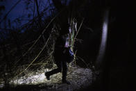 A young child walks alone through the brush after being smuggled across the Rio Grande river in Roma, Texas, Wednesday, March 24, 2021. (AP Photo/Dario Lopez-Mills)
