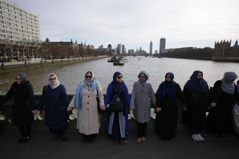 Tribute: Women activists wearing blue hold hands on Westminster Bridge in front of the Houses of Parliament to honour the victims of the March 22 attack (AFP/Getty Images)