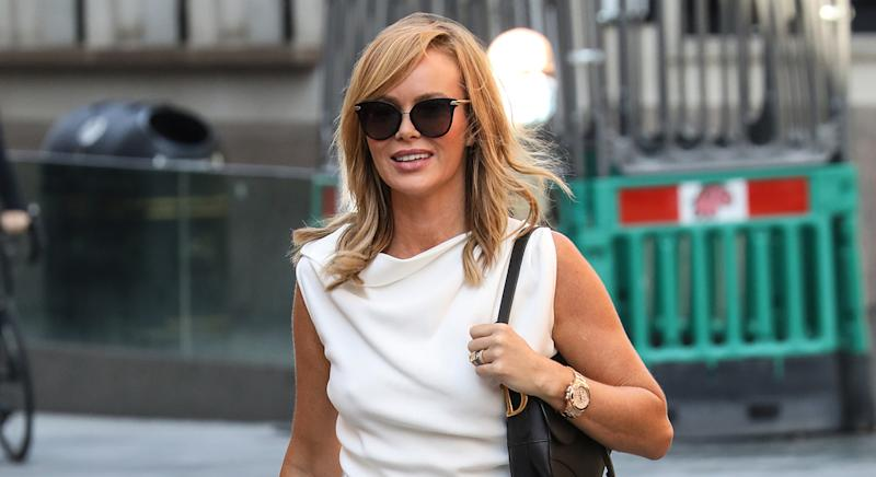 Amanda Holden dances around in chic white polka dot dress on heart Breakfast radio show - and it's on sale. (Getty Images)