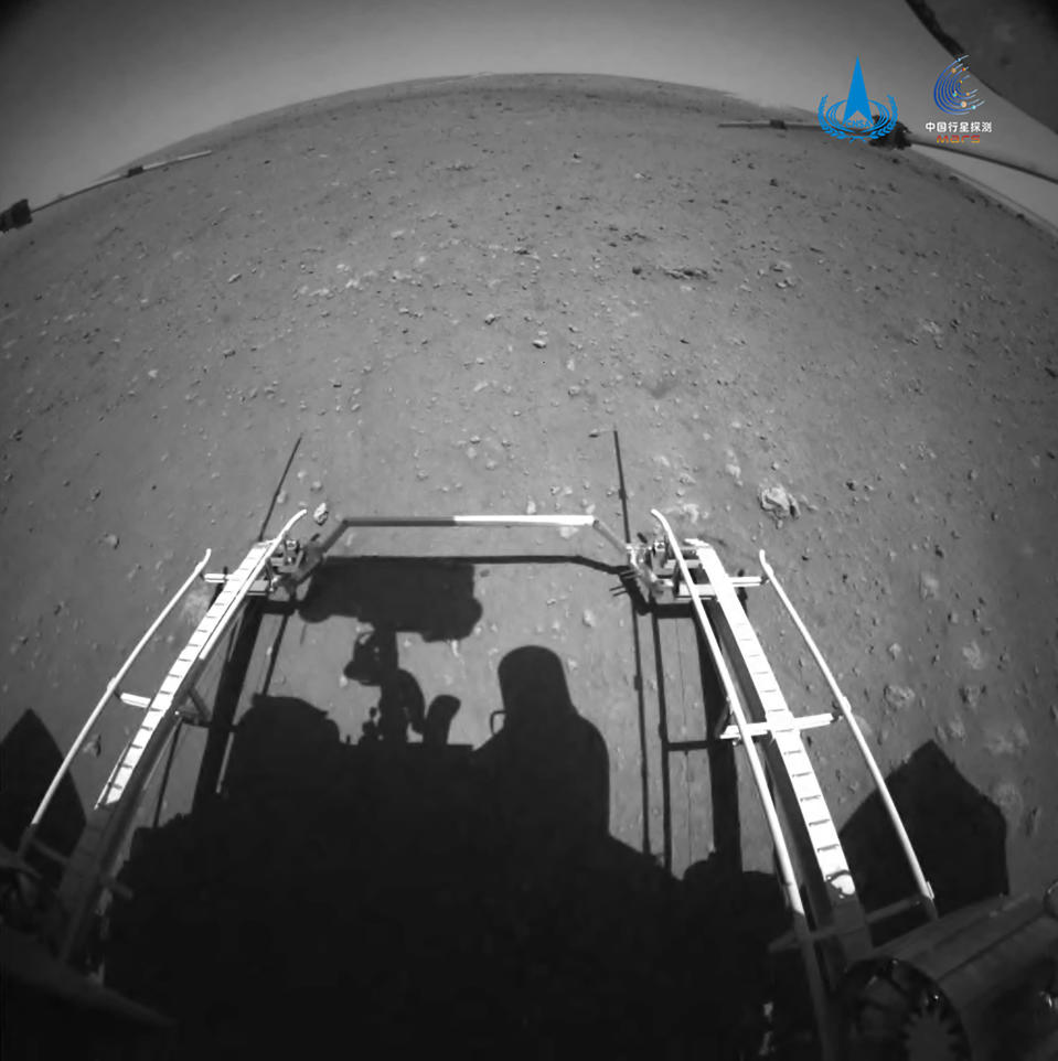 In this image released by the China National Space Administration (CNSA) on Saturday, May 22, 2021, a ramp and the surface of Mars are seen from a camera on the Chinese Mars rover Zhurong. China's first Mars rover has driven down from its landing platform and is now roaming the surface of the red planet, China's space administration said Saturday. (CNSA via AP)