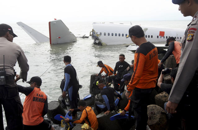 Indonesian divers get ready to retrieve a Lion Air jet plane's cockpit voice recorder out of the wreckage of the plane near the Ngurah Rai International airport in Kuta, Bali, Indonesia on Monday, April 15, 2013. The Indonesian passenger jet carrying 108 people missed the runway as it came into land on the resort island on Saturday, slamming into the water at high speed and splitting in two. (AP Photo/Firdia Lisnawati)