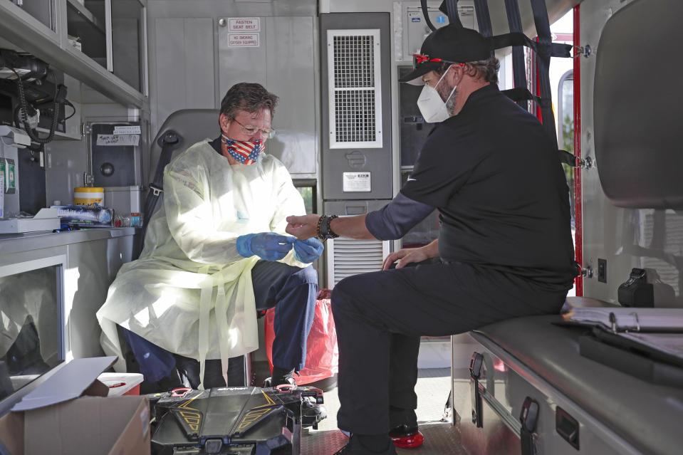 In this Saturday, May 9, 2020 photo, photographer Jason Vinlove, right, gets tested for COVID-19 antibodies before covering UFC 249 mixed martial arts event in Jacksonville, Fla.  There is no universal playbook for coronavirus testing in professional sports. Protocols and procedures, guidelines and handbooks, they could be as different as the rulebooks that govern leagues around the world. UFC performed nasal swabs and/or blood tests for roughly 1,200 people on site during its weeklong stay in Jacksonville, part of the mixed martial arts behemoth's health and safety protocols. (AP Photo/John Raoux)