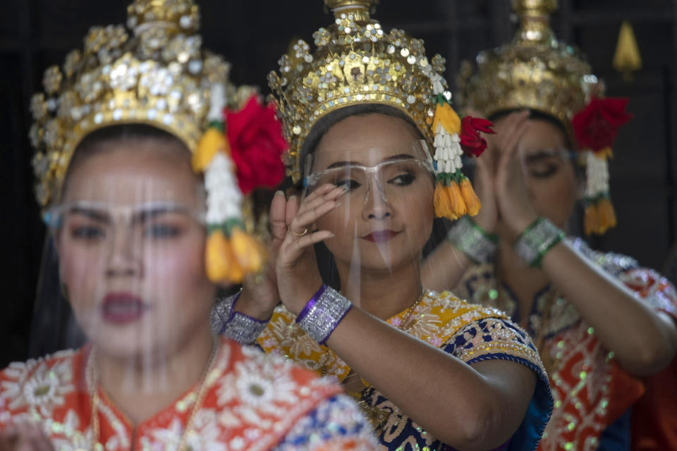 Thai classical dancers wearing face shields to help curb the spread of the coronavirus perform at the Erawan Shrine in Bangkok, Thailand, Tuesday, Jan. 12, 2021. Thailand's government announced new measures, including partial lockdowns with strict travel restrictions in some areas. Schools, bars, gambling parlors and other public gathering places have been closed. (AP Photo/Sakchai Lalit)