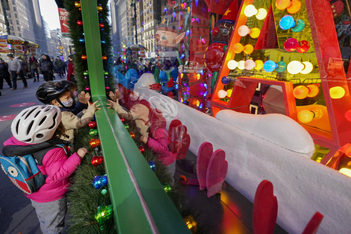 Children inspect the holiday windows display at the Macy's flagship store, Friday, Nov. 20, 2020, in New York. Macy's 2020 holiday windows honors essential workers and first responders during the coronavirus pandemic. (AP Photo/Mary Altaffer)