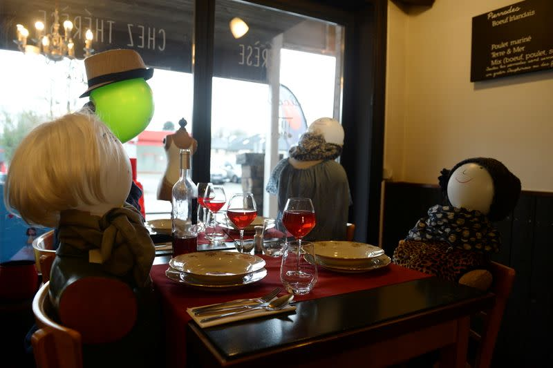 Mannequins with balloon heads representing customers sit on chairs in a closed restaurant in Rixensart