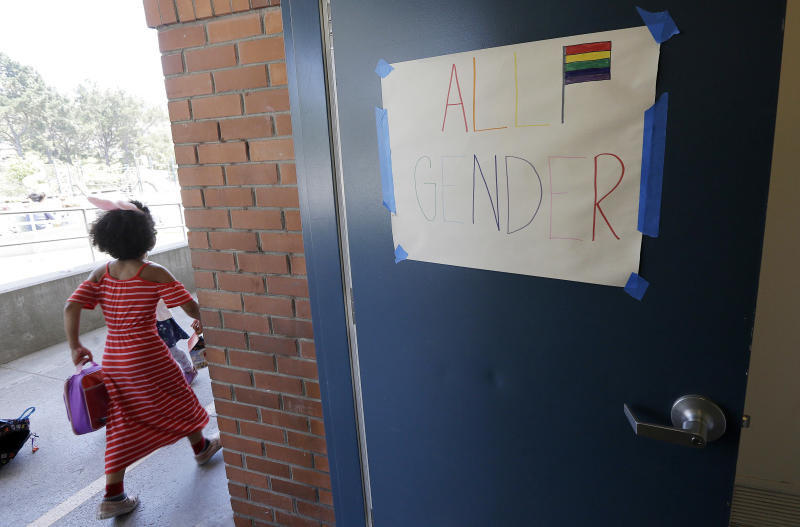 """In this Tuesday, July 11, 2017 photo, a camper walks past a sign for an all gender bathroom at the Bay Area Rainbow Day Camp in El Cerrito, Calif. The camp caters to transgender and """"gender fluid"""" children, aged 4-12, making it one of the only camps of its kind in the world open to preschoolers, experts say. (AP Photo/Jeff Chiu)"""