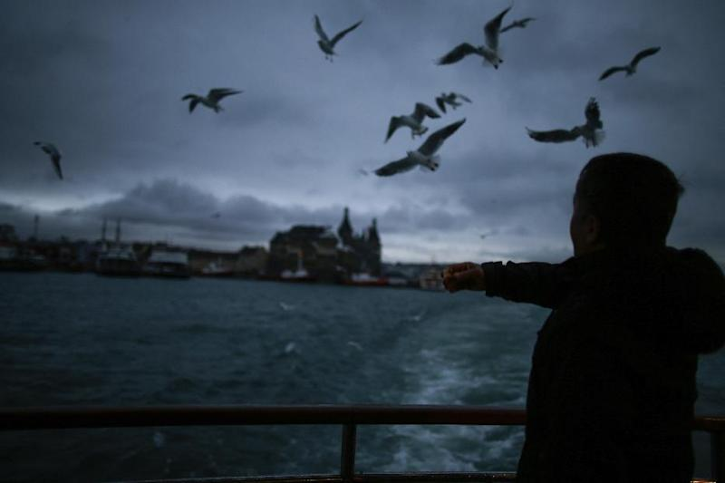 In this photo taken on Friday, Jan. 6, 2017, seagulls fly over a boat crossing the Bosporus Strait on a boat in Istanbul. These days, with a string of terror attacks targeting Istanbul still fresh in his memory, some residents say they are adapting their daily routines because of fears they could become the latest victims of violent extremism. (AP Photo/Emrah Gurel)
