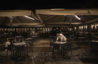 A waiter closes the terrace of a bar on the Mayor square in downtown Madrid, Spain, Friday, Oct. 23, 2020. (AP Photo/Manu Fernandez)