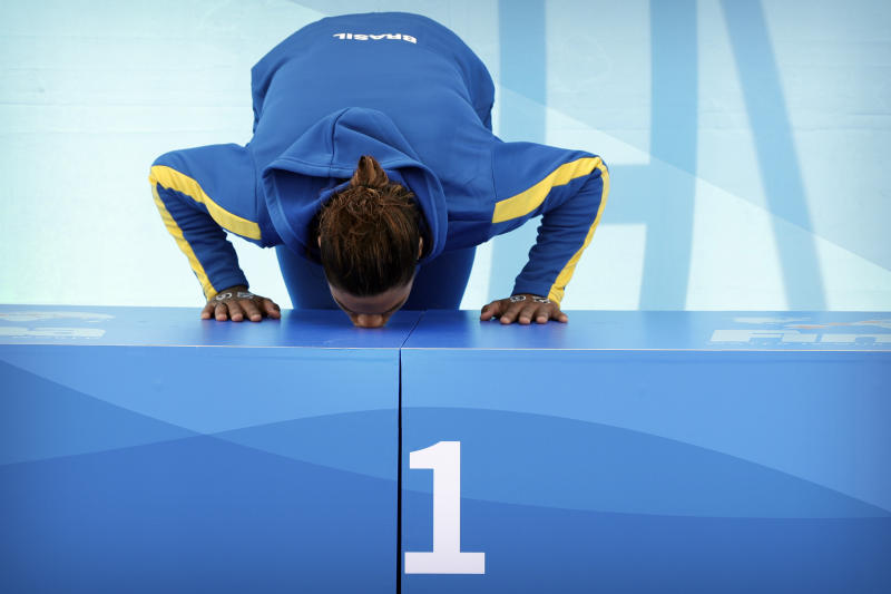 Gold medalist Ana Marcela Cunha of Brazil kisses the podium after the women's 5km open water swim at the World Swimming Championships in Yeosu, South Korea, Wednesday, July 17, 2019. (AP Photo/Mark Schiefelbein)