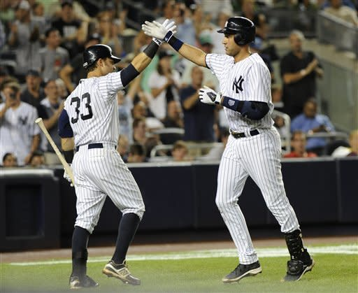 New York Yankees' Nick Swisher (33) greets Derek Jeter at home plate after Jeter hit a solo home run off of Boston Red Sox Franklin Morales in the fifth inning of a baseball game on Friday, Aug., 17, 2012, at Yankee Stadium in New York. Swisher hit a solo home run in the first inning. (AP Photo/Kathy Kmonicek)