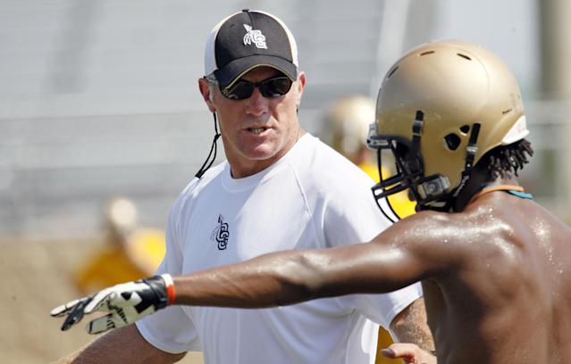 Former NFL quarterback Brett Favre, now an assistant football coach at Oak Grove High School in Hattiesburg, Miss., explains a pass route to receiver Shane McClendon during the first day of official practice for the fall high school football season, Monday, July 30, 2012. (AP Photo/Rogelio V. Solis)