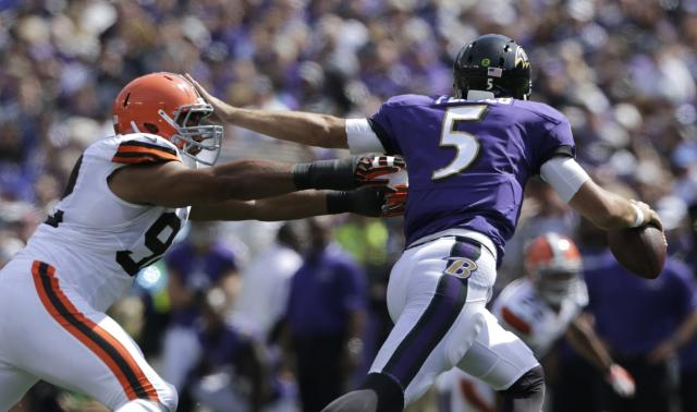Baltimore Ravens quarterback Joe Flacco (R) stiff arms Cleveland Browns defensive lineman Desmond Byrant (L) in the first half of their NFL football game in Baltimore September 15, 2013. REUTERS/Gary Cameron (UNITED STATES - Tags: SPORT FOOTBALL)