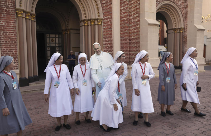 Catholic nuns surround a life size cut out of Pope Francis at the Assumption Cathedral in Bangkok, Thailand, Wednesday, Nov. 20, 2019. Pope Francis is heading to Thailand to encourage members of a minority Catholic community in a Buddhist nation and highlight his admiration for their missionary ancestors who brought the faith centuries ago and endured persecution. (AP Photo/Manish Swarup)