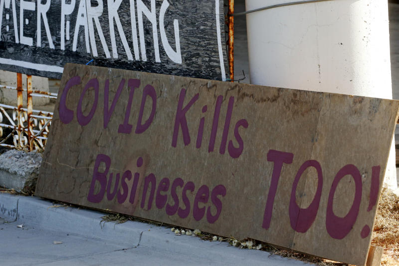 """A """"covid kills businesses too"""" sign is shown outside Euro Treasures Antiques Friday, April 24, 2020, in Salt Lake City. Scott Evans is closing his art and antique store after 40 years. This year started out well for his business, then COVID-19 hit, along with shelter-in-place orders. With a drastic drop in customers, Evans says it was no longer cost effective to stay open. (AP Photo/Rick Bowmer)"""
