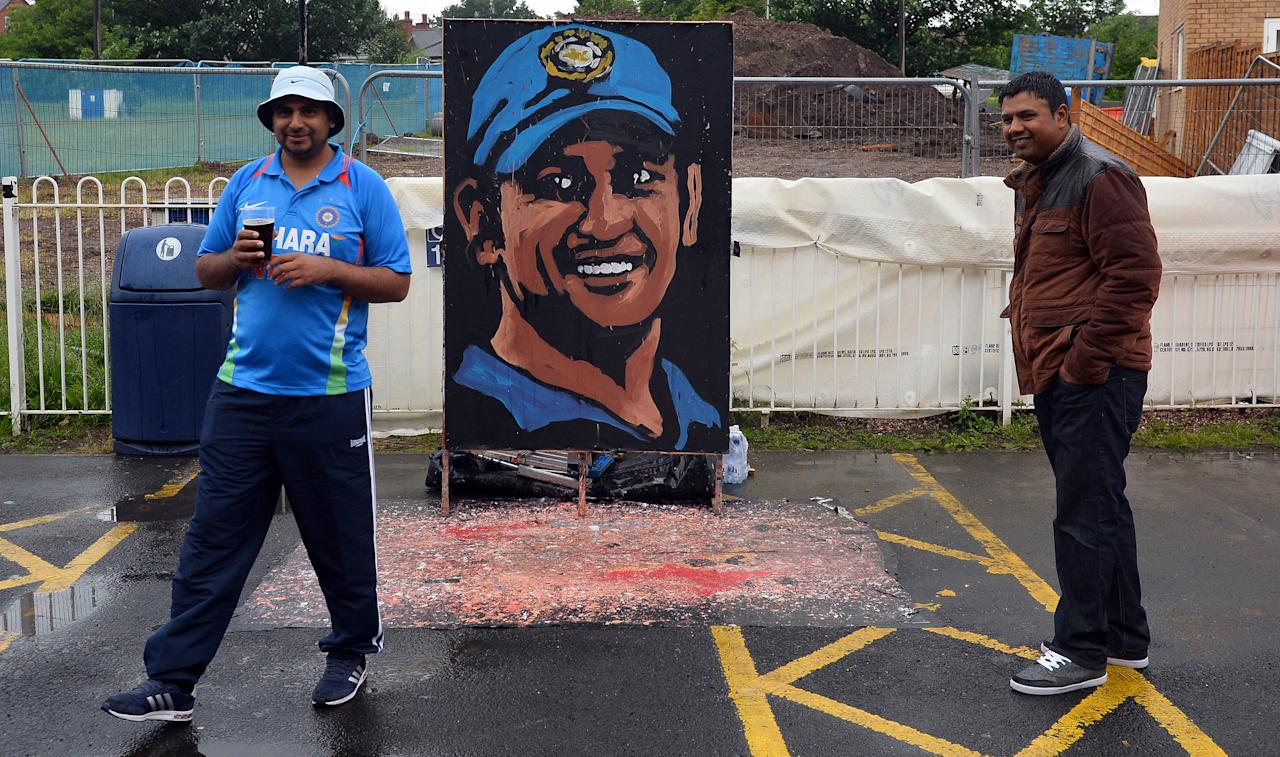 A painting of Indian captain Mahendra Singh Dhoni is seen as rain delays the start of play in the 2013 ICC Champions Trophy Final cricket match between England and India at Edgbaston in Birmingham, central England on June 23, 2013. AFP PHOTO/PAUL ELLIS - RESTRICTED TO EDITORIAL USE -