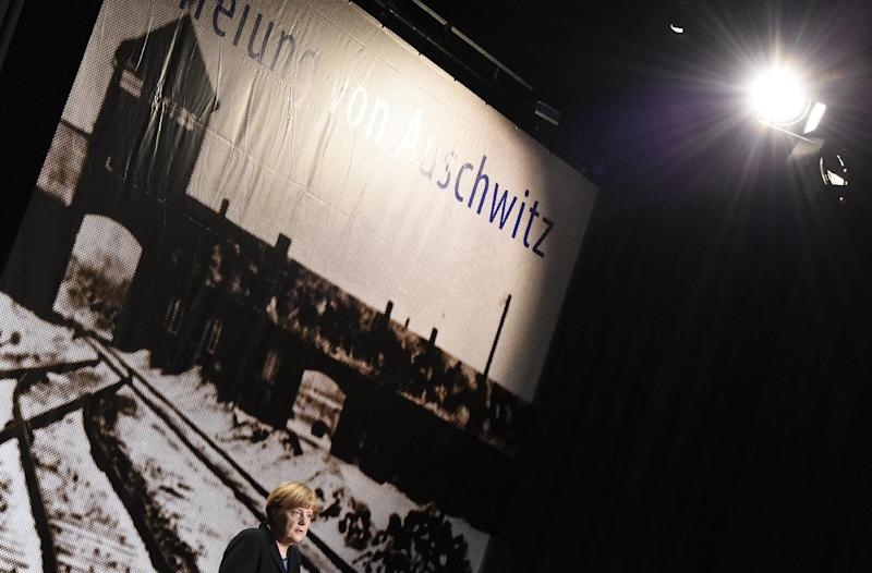 German Chancellor Angela Merkel stands in front of a picture of the Auschwitz concentration camp as she gives a speech during the International Auschwitz Committee ceremony to mark the 70th anniversary of its liberation on January 26, 2015 in Berlin